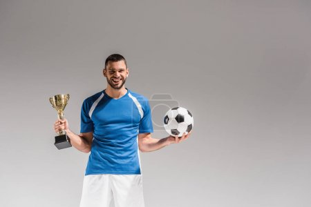 Cheerful sportsman holding football and golden champions cup on grey background