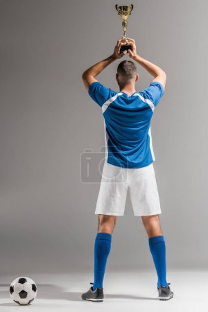 Back view of sportsman holding golden trophy near football on grey background