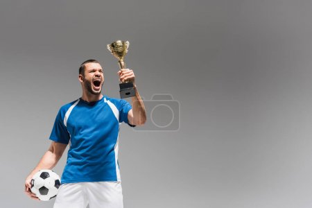 Astonished sportsman looking at golden champions trophy while holding football isolated on grey