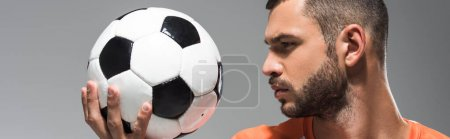 Bearded man looking at football isolated on grey, banner