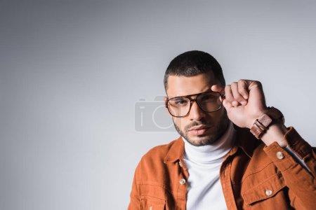 Photo pour Homme regardant la caméra tout en tenant des lunettes élégantes sur fond gris - image libre de droit