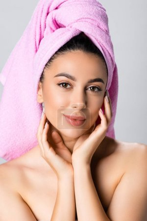 Photo for Beautiful woman with towel on hair touching face isolated on grey - Royalty Free Image
