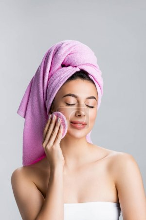 Photo for Beautiful woman with towel on hair using sponge with closed eyes isolated on grey - Royalty Free Image
