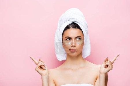 Photo pour Cher belle femme avec serviette sur les cheveux et hydrogel patchs oeil sur le visage pointant avec les doigts isolés sur rose - image libre de droit