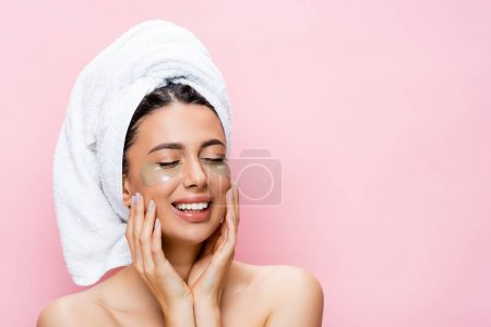 Photo for Smiling beautiful woman with towel on hair and hydrogel eye patches on face isolated on pink - Royalty Free Image