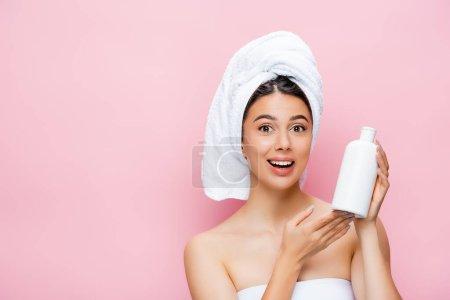 glücklich schöne Frau mit Handtuch auf dem Haar und Flasche Lotion isoliert auf rosa
