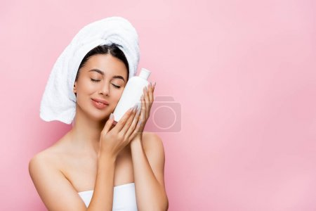 beautiful woman with closed eyes, towel on hair and bottle of lotion isolated on pink