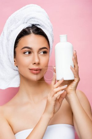 Photo for Beautiful woman with towel on hair and bottle of lotion isolated on pink - Royalty Free Image