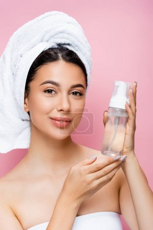 smiling beautiful woman with towel on hair and cleansing foam isolated on pink