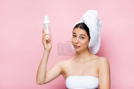 beautiful woman with towel on hair and cleansing foam isolated on pink