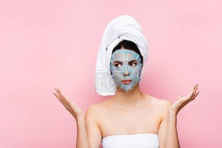 Photo pour Belle femme avec feuille de masque sur le visage montrant haussement d'épaules isolé sur rose - image libre de droit