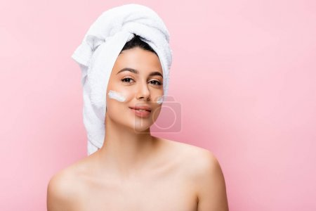 beautiful woman with towel on hair and cosmetic cream on face isolated on pink