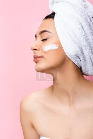schöne Frau mit Handtuch auf dem Haar, geschlossenen Augen und kosmetischer Creme im Gesicht isoliert auf rosa
