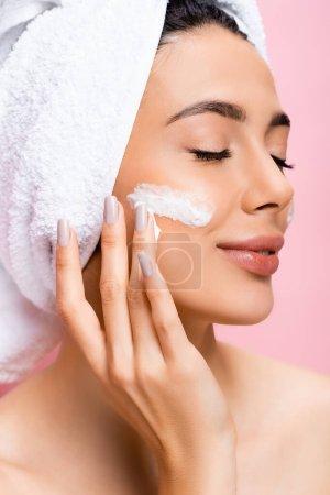 Photo pour Belle femme avec serviette sur cheveux, yeux fermés et crème cosmétique sur le visage isolé sur rose - image libre de droit