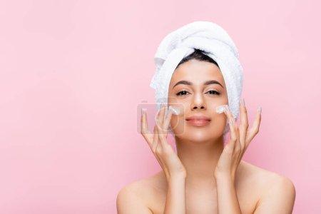 Photo pour Belle femme avec serviette sur cheveux et crème cosmétique sur le visage isolé sur rose - image libre de droit