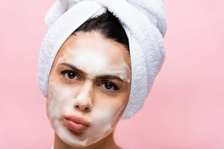 beautiful woman with towel on hair and foam on face grimacing isolated on pink