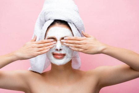 beautiful woman with towel on head and clay mask on face covering eyes isolated on pink