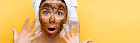 Photo for Shocked beautiful woman with towel on head and coffee mask on face isolated on yellow, banner - Royalty Free Image