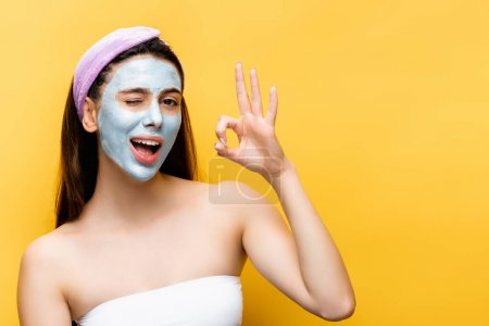 Photo pour Belle femme avec masque en argile sur le visage montrant OK isolé sur jaune - image libre de droit