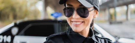portrait of happy policewoman looking at camera on blurred background outdoors, banner