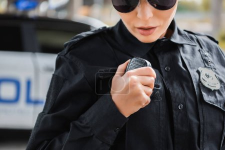 cropped view of young policewoman talking on radio set on blurred background outdoors