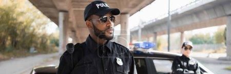 grave policier afro-américain regardant loin avec un collègue flou sur fond de rue urbaine, bannière