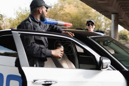 Photo for Happy policewoman leaning on patrol car near african american colleague on blurred background outdoors - Royalty Free Image