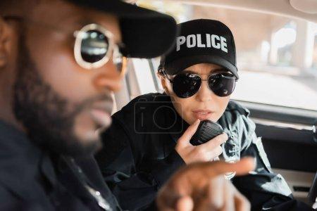 Photo pour Policier parler sur le poste de radio avec un collègue afro-américain flou au premier plan en voiture de patrouille - image libre de droit