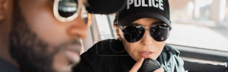 serious policewoman talking on radio set near blurred african american policeman on foreground in patrol car, banner