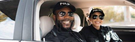 oficiales de policía multiculturales felices mirando la cámara en el coche patrulla sobre fondo borroso, pancarta