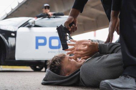 Photo pour Policier afro-américain visant avec un pistolet au délinquant effrayé couché dans la rue sur fond flou - image libre de droit