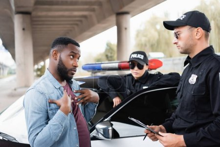 victime afro-américaine irritée gestuelle tout en se disputant avec un policier avec une policière floue en arrière-plan à l'extérieur