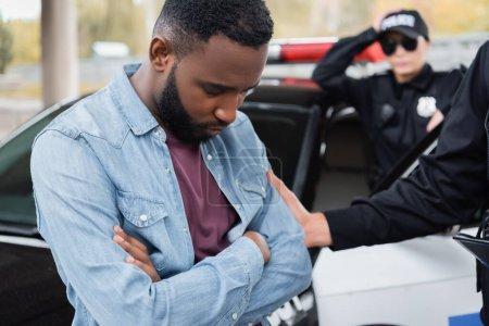 Photo pour Triste victime afro-américaine debout près d'un policier et voiture à l'extérieur - image libre de droit