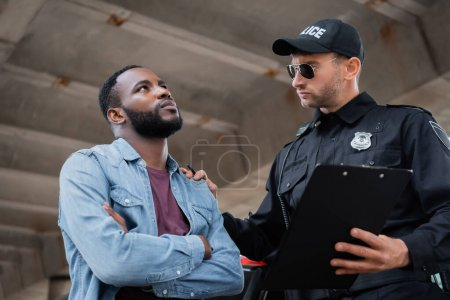 Police officer calming african american victim while holding clipboard on blurred foreground outdoors