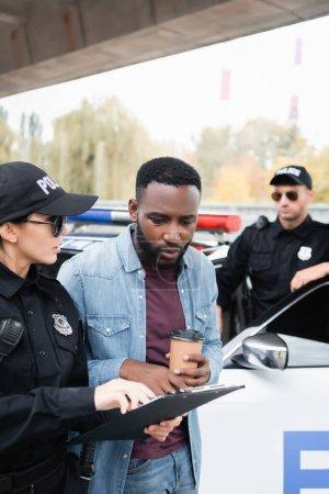 Photo pour Policewoman tenant presse-papiers près de victime afro-américaine avec café pour aller et collègue près de la voiture sur fond flou - image libre de droit