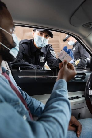 Police officer in medical mask looking at african american driver holding license in car on blurred foreground