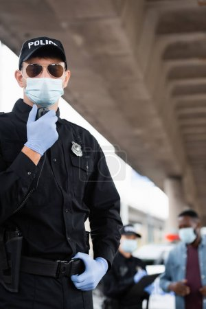 Police officer in medical mask and latex gloves using walkie talkie near colleague and african american man on blurred background on urban street