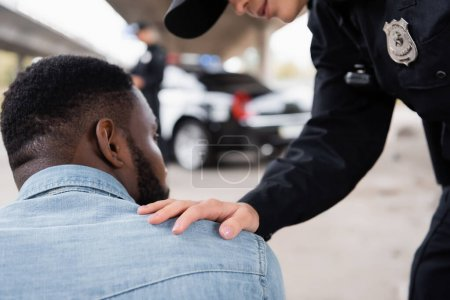 Policewoman calming african american victim on urban street