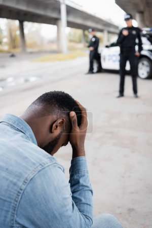 Photo for Sad african american victim near police officers and car on blurred background outdoors - Royalty Free Image