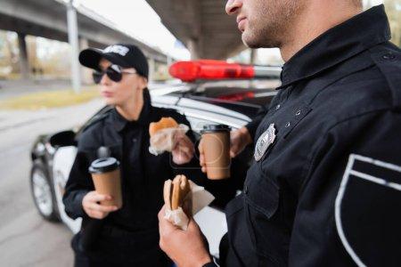 Photo pour Un policier tenant un hamburger et un café pour s'approcher d'un collègue et d'une voiture sur fond flou dans une rue urbaine - image libre de droit