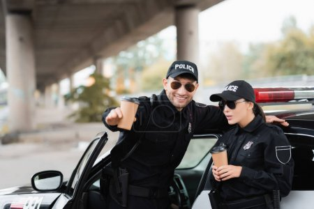 Photo for Cheerful police officer pointing with hand near colleague holding coffee to go and car outdoors - Royalty Free Image