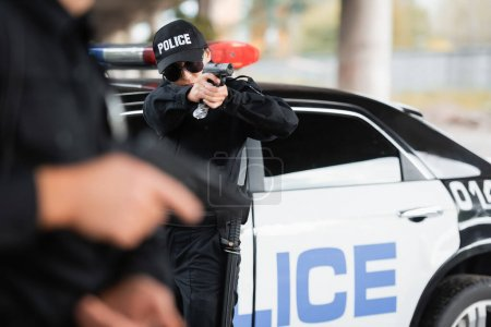 Photo for Policewoman in sunglasses holding gun near colleague on blurred foreground and car outdoors - Royalty Free Image