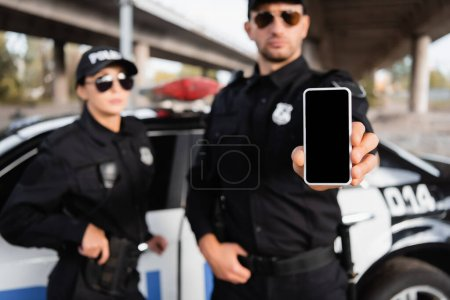 Smartphone with blank screen in hand of policeman near colleague and car on blurred background