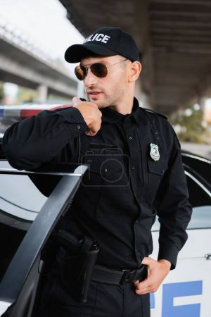 Policeman in sunglasses using walkie talkie near car on urban street