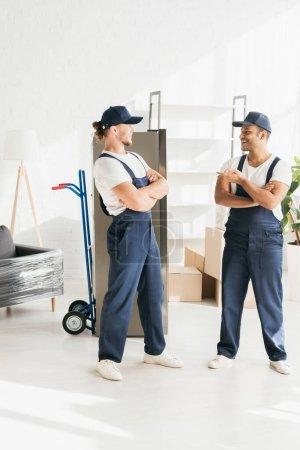 Photo pour Heureux déménageur indien pointant sur un collègue en chapeau debout avec les bras croisés sur l'appartement - image libre de droit