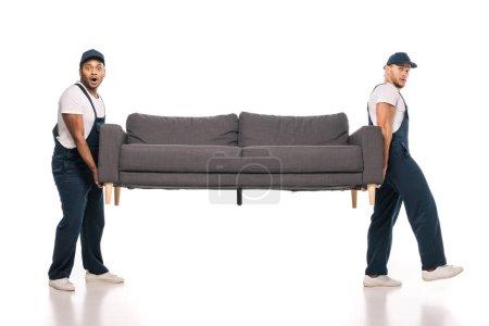 Foto de Longitud completa de los que se mueven multiculturales sorprendidos llevando sofá en blanco - Imagen libre de derechos