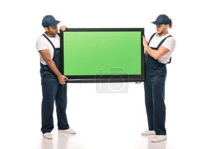 Photo pour Pleine longueur de déménageurs multiculturels surpris portant TV plasma avec écran vert sur blanc - image libre de droit