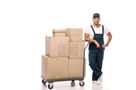 Photo pour Pleine longueur de déménageur indien joyeux en salopette debout avec la main sur la hanche près du camion à main avec des boîtes en carton sur blanc - image libre de droit