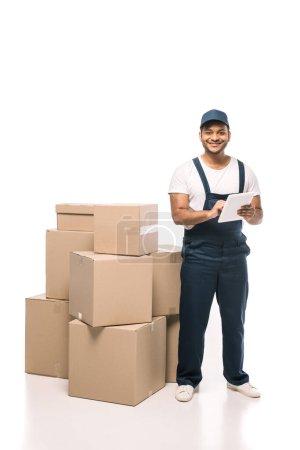 Photo pour Joyeux déménageur indien en salopette en utilisant une tablette numérique près de boîtes en carton sur blanc - image libre de droit