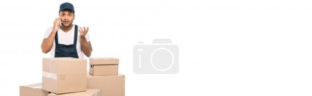 Photo for Displeased indian mover in overalls talking on smartphone near carton boxes isolated on white, banner - Royalty Free Image